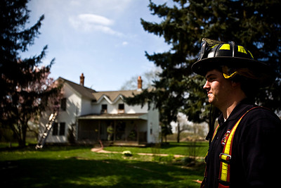 Lance Booth - lbooth@shawmedia.com Kelly Connor, of the Spring Grove Fire Department, stands in front of a house after helping to put out the fire at 10105 Winn Road in Spring Grove on Thursday, March 22, 2012. No injuries were reported and the cause of the fire has yet to be determined.