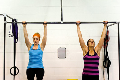 "Daniel J. Murphy - dmurphy@shawmedia.com  Nicole Bobula of Hoffman Estates (left) and Leadia Jarvis of Crystal Lake (right) practice a ""kipping pull-up"" Friday March 23, 2012 at Cross Fit AMRAP in Crystal Lake."
