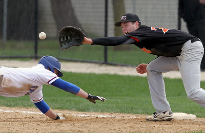 Sarah Nader - snader@shawmedia.com St. Charles East's John Hondlik (right) waits for the pass while Dundee-Crown's Nick Hathon slides safely back to first after trying to steal for second during the third inning of Monday's game in Carpentersville on March 25, 2012. St. Charles East won, 1-11.