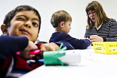 Lance Booth - lbooth@shawmedia.com Abbas Peera, left, 5, Conrad Herff, 5, and Tiffany Herff, all of Cary, make crafts at the Cary Library on Tuesday, March 27, 2012. The Cary and Fox River Grove library districts are going to have a discussion on consolidating the libraries on April 4th.