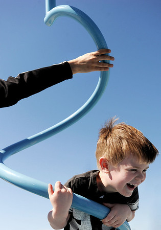 Sarah Nader - snader@shawmedia.com Seth Petersen, 4, of Crystal Lake holds on tight while his uncle spins him around while playing at Three Oaks Recreation Area in Crystal Lake on Wednesday, March 28, 2012.