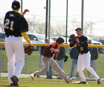 Mike Greene - For the Northwest Herald Jacobs' Max Rider (right) prepares to receive a pick-off attempt from teammate Greg Mixon as Brother Rice's Brian Mcquillan slides back to the base Saturday in Algonquin. Mcquillan was safe on the play.