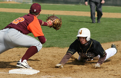 Mike Greene - For the Northwest Herald Jacobs' Aaron Traub (right) slides back to first base during a pick-off attempt as Brother Rice's Kyle Bernaciak await the ball Saturday in Algonquin. Traub was safe on the play.