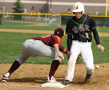 Mike Greene - For the Northwest Herald Jacobs' Ryan Ulmer (right) gets back to first base safely on a pick-off play during a game against Brother Rice Saturday in Algonquin. The Eagles lost to the Crusaders 4-3.