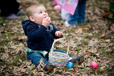 Jenny Kane - jkane@shawmedia.com McHenry resident, 10-month-old Lincoln Uhlmann tries to eat one of his plastic easter eggs after the Woodstock Jaycees's annual Easter Egg Hunt at the Hilltop Pavilion at Emricson Park in Woodstock on Saturday.