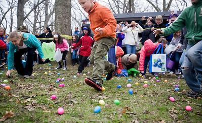 Jenny Kane - jkane@shawmedia.com Tristan Carter, (center) gathers eggs during the Woodstock Jaycees's annual Easter Egg Hunt at the Hilltop Pavilion at Emricson Park in Woodstock on Saturday.