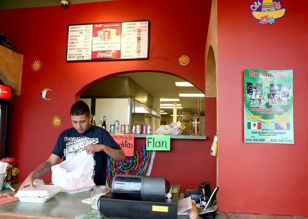 Sandy Bressner - sbressner@shawmedia.com<br /> Jamie Rojas gets an order ready for take-out at the new location of Chico's Tacos on Valley Drive in Elburn.