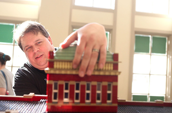 Sandy Bressner - sbressner@shawmedia.com<br /> Roger Snow of Bartlett places the dome onto his LEGO replica of the Old Kane County Courthouse in Geneva in preparation for the Northern Illinois LEGO Train Club Exhibition at the Geneva History Center.