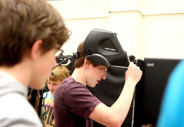 Sandy Bressner - sbressner@shawmedia.com<br /> Kaneland High School junior Jimmy Merletti tries on a welder's mask during a college and career fair at the school Thursday.
