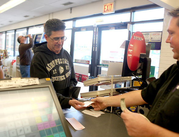 Sandy Bressner - sbressner@shawmedia.com<br /> Sammy Ortegon of St. Charles buys a Mega Millions ticket from Steve Davison at Davison's 7-Eleven in St. Charles Thursday afternoon. The odds of winning the jackpot are about one in 176 million. The winning ticket must match the five numbers drawn, plus the Megaball number.