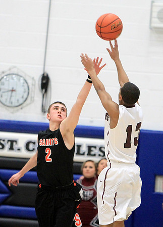 Sandy Bressner - sbressner@shawmedia.com<br /> St. Charles East's Dominic Adduci tries to block a shot by Elgin's Cortez Scott during the second half of East's 57-52 regional final game loss to Elgin Friday at St. Charles North.