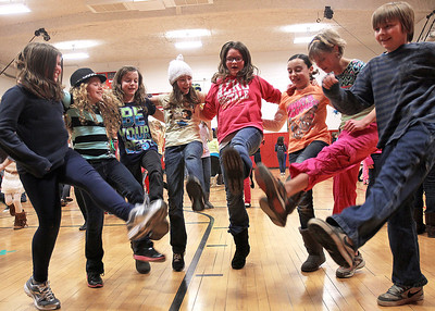 """Monica Maschak - mmaschak@shawmedia.com A group of friends kick up their legs and dance to """"Cotton Eyed Joe"""" at the Preteen Jam hosted by the McHenry Parks and Recreation Department at Duker School on Friday, March 1, 2013. Fourth and fifth graders from District 15 schools were all invited to participate in dancing, games, door prizes and more."""