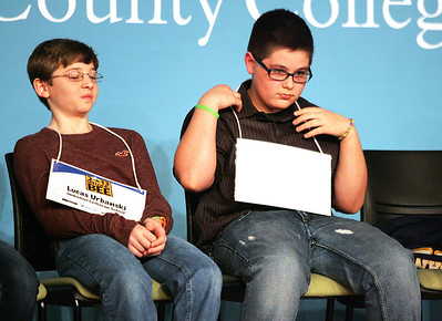 Monica Maschak - mmaschak@shawmedia.com Alexander Joseph (right), of School District 200, flips over his name tag after mispelling a word in the first round of The Annual McHenry County Spelling Bee on Wednesday, March 6, 2013. Stew Cohen of Star 105.5 was  the pronouncer for the Bee.