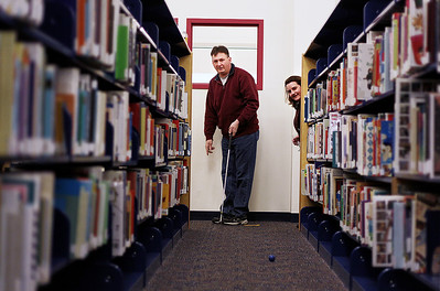 Sarah Nader - snader@shawmedia.com Bill Ryan (left) of Crystal Lake and his wife, Beth, play a game of miniature golf while attending Mini Links Library After Dark at the Woodstock Public Library on Friday, March 15, 2013. Transformed by the Friends of Woodstock Public Library the library featured an 18-hole miniature golf course that covered all three levels of the library. The event continues on Saturday from 10 a.m. to 3 .p.m. for families and children.
