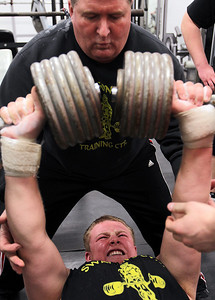 Sarah Nader - snader@shawmedia.com Gary Swanson (top) spots for his son, Dominic, 14, while he lifts 105 pounds on each arm while training at Swanson's Gym in their garage in Union on Saturday, March 16, 2013. Swanson runs the gym in his garage for powerlifters, which include a couple of D-I athletes from Huntley.