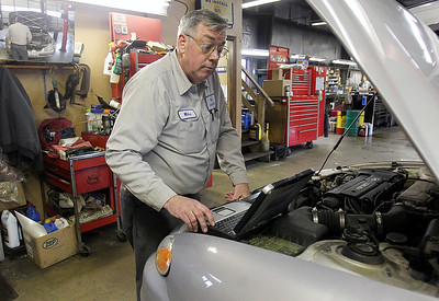 Sarah Nader - snader@shawmedia.com Mike Fraser, owner of Mike's Service Center in Crystal Lake works on a car in his shop on Monday, March 18, 2013. This year the company is celebrating 30 years in business.