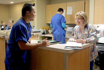 Sarah Nader - snader@shawmedia.com RN J.C. Jimeno of Carpentersville talks with his co-worker Kris Piefer while working at Centegra Hospital in McHenry on Monday, March 25, 2013.