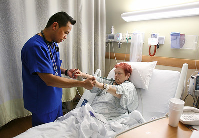 Sarah Nader - snader@shawmedia.com RN J.C. Jimeno of Carpentersville check on Dawn Davis of McHenry while working at Centegra Hospital in McHenry on Monday, March 25, 2013.