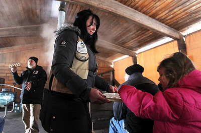 Monica Maschak - mmaschak@shawmedia.com At the end of the Festival of the Sugar Maples tour at Coral Woods Conservation Area, volunteer Ashley Cokley hands out samples of pure maple syrup for attendees to try.