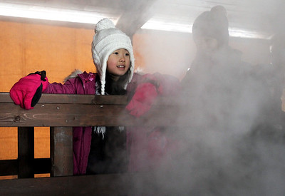 Monica Maschak - mmaschak@shawmedia.com Mei Yano, 7, looks at the steam from the evaporator where sap was being turned into maple syrup at the Festival of the Sugar Maples at Coral Woods Conservation Area on Saturday, March 2, 2013. Anyone could take a tour and learn how maple syrup was discovered, how maple trees produce sap and how sap is collected from trees.