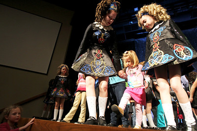 Monica Maschak - mmaschak@shawmedia.com Nicole Navarro (left) and Claire Gilhooly (right), with the Rebecca McCarthy School of Dance, teach Navarro's cousin Hailey Haiges, 3, how to Irish Step Dance on stage at Springbrook Community Church after the third annual St. Patricks Day Festival on Friday, March 8, 2013. The event featured a bagpiper, traditional Irish dance, raffle baskets, authentic Irish vendors and more.