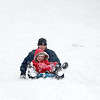 Matt Tompkins of Elburn sleds down the hill at Johnson's Mound with his daughter, Ashlee, 9, during Tuesday's snowstorm. (Sandy Bressner photo)