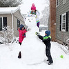 (Left to right) Emma Gerwig, 10, Audrey Wetzel, 11, and Charlie Wetzel, 6, build a giant snowman outside Gerwig's Geneva home during Tuesday's snowstorm. (Sandy Bressner photo)