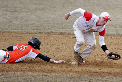 Sarah Nader - snader@shawmedia.com McHenry's Jordan Witbeck (left) slides back to second in just enough time as Marian Central's Tyler Hickey catches the pass during the fifth inning of Wednesday's game at Peterson Park on March 27, 2013. McHenry won, 8-0.