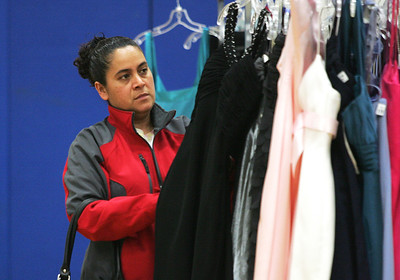 Monica Maschak - mmaschak@shawmedia.com Maria Pelayo looks at dresses for her daughter to try on in hopes that they can find a prom dress for $25 at the My Sister's Dress fundraiser for Big Brothers Big Sisters of McHenry County on Saturday, March 9, 2013. Gently used dresses were donated and sold for girls going to prom or other special occasions at McHenry County College.
