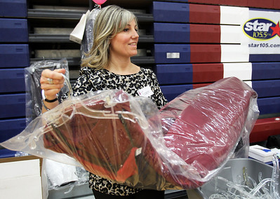 Monica Maschak - mmaschak@shawmedia.com Volunteer for Big Brothers Big Sisters Gwen Fehrman bags a couple of purchased dresses for customers during the My Sister's Dress fundraiser at McHenry County College on Saturday, March 9, 2013. Gently used dresses were donated and sold for $25.