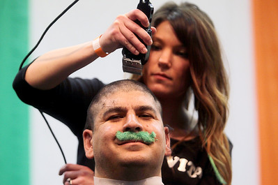 Sarah Nader - snader@shawmedia.com Vito Deiure of Lake in the Hills has his head shaved by volunteer Jenny Neuman of Barrington while attending the fifth annual Shamrock Shave at St. Margaret Mary's School in Algonquin on Saturday, March 16, 2013. More than 50 men, women and children shaved their heads to raise money for community families in need and for cancer research.