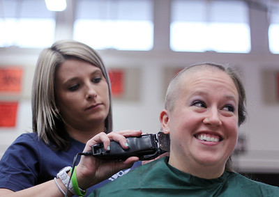 Sarah Nader - snader@shawmedia.com Volunteer Natalie May (left) shaves Michelle Roberts long hair  while participating in the St. Baldrick's Day McHenry Community Shave at McHenry High School on Thursday, March 14, 2013.