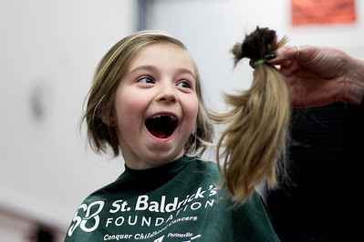 Sarah Nader - snader@shawmedia.com Sienna Begley, 7, of McHenry reacts to seeing her pony tail cut off while she participated in the St. Baldrick's Day McHenry Community Shave at McHenry High School on Thursday, March 14, 2013. The fundraising event reached their goal of being number one in the world for the number of people shaving their heads at a single event for St. Baldrick's Day. Over 650 participants registered to have their heads shaved for charity.