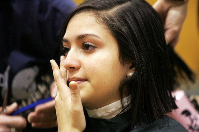 Monica Maschak - mmaschak@shawmedia.com Woodstock High School freshman Jessica Zarate wipes away tears as her hair is chopped to a short length in front of the whole school for the St. Baldrick's Foundation on Friday, March 15, 2013. Students and staff members went bald the day after community members shaved their heads for the foundation, raising more than $15,000.