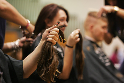 Monica Maschak - mmaschak@shawmedia.com Participants hold up their locks of hair as they are cut off during the Woodstock High School St. Baldrick's event held on Friday, March 15, 2013. Students, staff and community members raised more than $15,000 for the foundation.