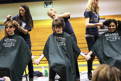 Monica Maschak - mmaschak@shawmedia.com Woodstock High School students Hannah Little (left), senior, Nora Brown, sophomore, and Keren Figueroa, sophomore hold hands as they prepare to get their heads shaved in front of the whole school for the St. Baldrick's Foundation on Friday, March 15, 2013. Students and staff members went bald the day after community members shaved their heads for the foundation, raising more than $15,000.