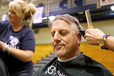 Monica Maschak - mmaschak@shawmedia.com Woodstock High School teacher Herb Kruse has his hair shaved in front of the whole school for the St. Baldrick's Foundation on Friday, March 15, 2013. Students and staff members went bald the day after community members shaved their heads for the foundation, raising more than $15,000.
