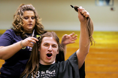 Monica Maschak - mmaschak@shawmedia.com Junior Maitiu Sexton holds up his first-cut lock of hair for the entire school to see at the Woodstock High School St. Baldrick's event held on Friday, March 15, 2013. Students, staff and community members raised more than $15,000 for the foundation.