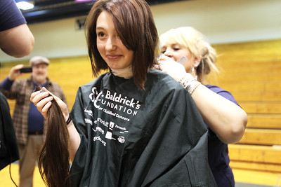Monica Maschak - mmaschak@shawmedia.com Woodstock senior Taylor Scheidler holds up her freshly chopped hair at the Woodstock High School St. Baldrick's event held on Friday, March 15, 2013. Students, staff and community members raised more than $15,000 for the foundation.