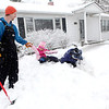 Dan Smith helps his daughter, Byrdie, 3, out of the snow as his son, Wylder, 4, plays nearby outside their Geneva home during Tuesday's snowstorm.(Sandy Bressner photo)