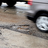Cars drive past a pothole on State Street in Geneva.(Sandy Bressner photo)