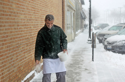 Sarah Nader - snader@shawmedia.com Chris Angelos, owner of Cafe Olympic salts the sidewalk outside his restaurant in Crystal Lake on Tuesday, March 5, 2013. Northern Illinois and northwest Indiana is under a winter storm warning until midnight and forecasters have predicted between 7 to 10 inches of snow throughout much of the Chicago region.