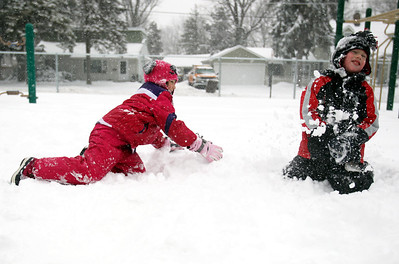 Monica Maschak - mmaschak@shawmedia.com Gavin Fujino (right), 7, braces for impact as Clara Alt, 7, throws a snowball and reaches for more snow at the Husmann Elementary School playground during a snowstorm Tuesday, March 5, 2013. Most schools closed due to the weather, which allowed children to go out and enjoy the snow.