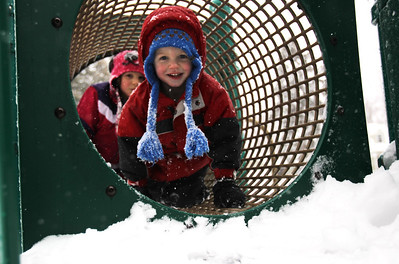 Monica Maschak - mmaschak@shawmedia.com Nolan Kenny, 3, crawls through a tube at the Husmann Elementary School playground during a snowstorm Tuesday, March 5, 2013. Most schools closed due to the weather, which allowed children to go out and enjoy the forecasted 7 to 10 inches of snow.