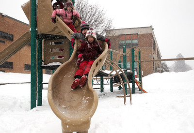 Monica Maschak - mmaschak@shawmedia.com Riley Kenny, 8, leads a chain of her friends as they slip down a snowy slide at the Husmann Elementary School playground during a snowstorm Tuesday, March 5, 2013. Most schools closed due to the weather, which allowed children to go out and enjoy the forecasted 7 to 10 inches of snow.