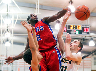 Sarah Nader- snader@shawmedia.com Dundee-Crown's Malik Dunner (left) blocks a shot by Crystal Lake South's Chris Mahoney during the third quarter of Monday's Crystal Lake Central Regional March 3, 2014. Dundee-Crown defeated Crystal Lake South, 61-52.