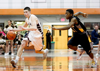 Sarah Nader- snader@shawmedia.com Prairie Ridge's Michael Bradshaw (left) is guarded by Jacobs' Mike Canady while he dribbles the ball towards the basket during the fourth quarter of Tuesday's Class 4A Crystal Lake Central Regional game March 4, 2014. Jacobs' defeated Prairie Ridge, 55-46.
