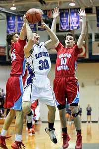 Michelle LaVigne/ For Shaw Media Hampshire's Austin Spaeth attempts to shoot past Marian's Nate Patterson and Nick Waytula  during the regional basketball game played in Woodstock on March 4, 2014. Marian Central won 62-61.