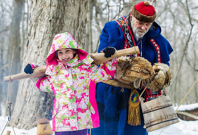 Kyle Grillot - kgrillot@shawmedia.com   Jerry Martin, dressed as an Anishinabe Native American demonstrates how maple sap was collected with the help of Monique Addison of Aldon-Hebron, 10,  during the annual Festival of the Sugar Maples at Coral Woods Conservation Area Saturday in Marengo.