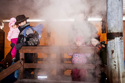 Kyle Grillot - kgrillot@shawmedia.com   Chuck Ruehl of Ingleside carries his daughter Lydia, 3, through the evaporation room during the annual Festival of the Sugar Maples at Coral Woods Conservation Area Saturday in Marengo.